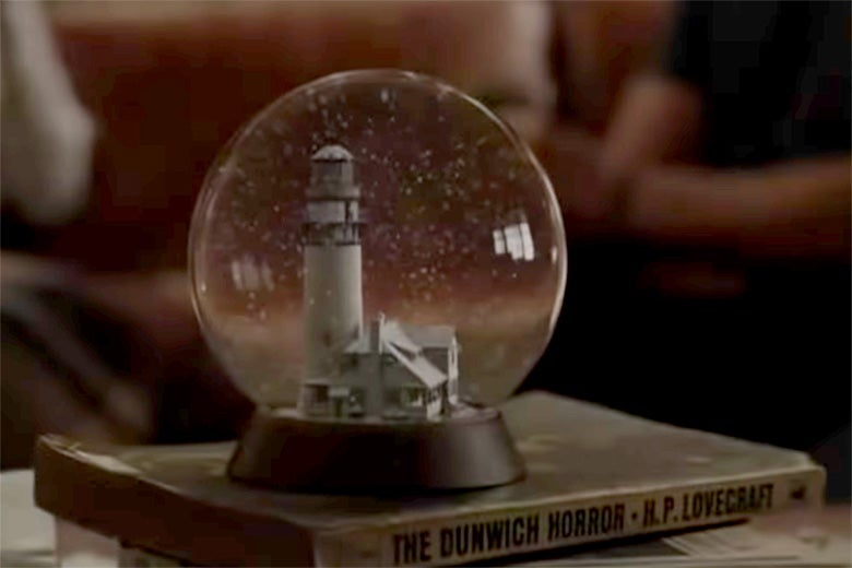 A snow globe on top of H.P. Lovecraft's The Dunwich Horror.