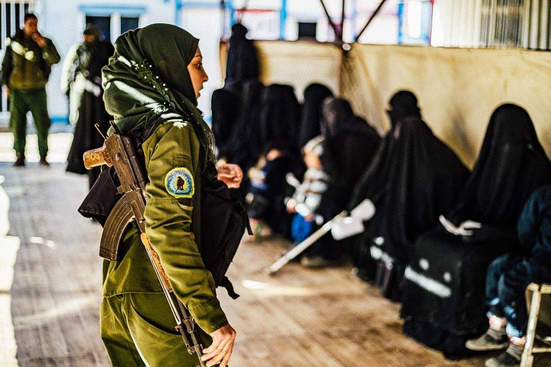 A female Kurdish fighter in uniform faces a row of women seated, wearing black veils.