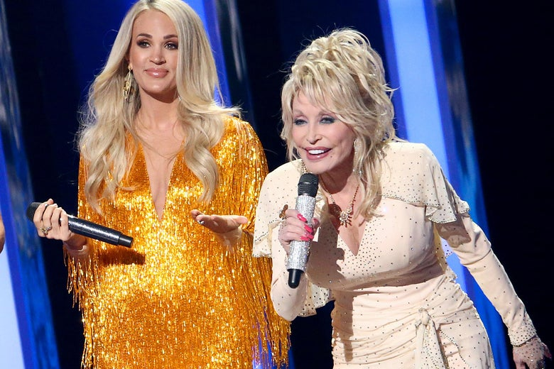 Dolly Parton leans forward holding a mic with Carrie Underwood standing beside her onstage during a performance at the 2019 CMAs