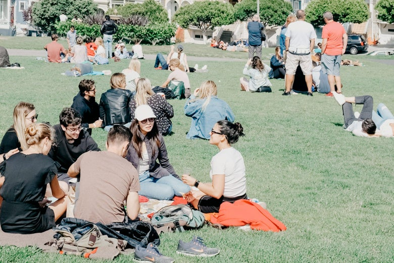 Groups of people sitting on blankets at a park.