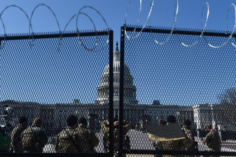 The Capitol seen through a fence with barbed wire on top. Soldiers in fatigues stand on the other side.