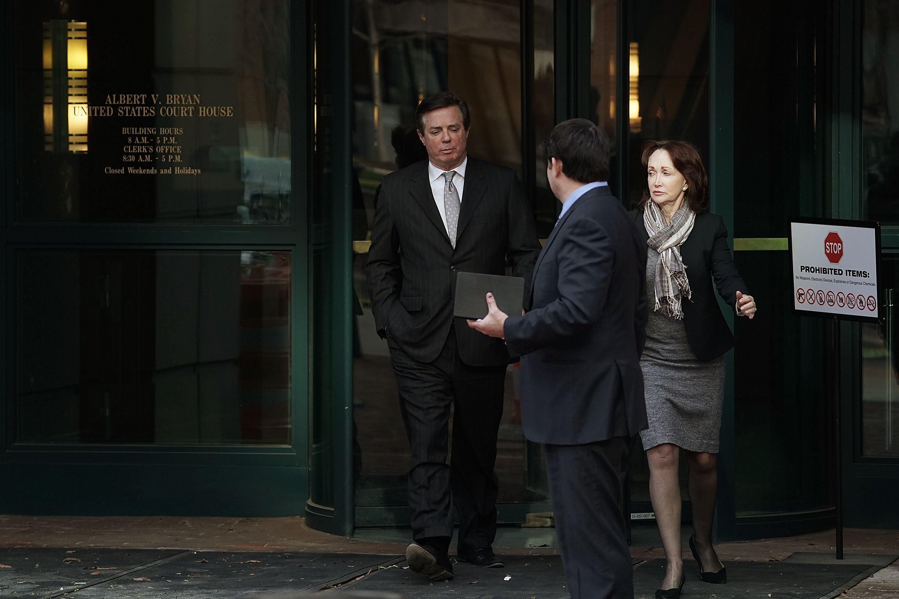 Paul Manafort exits a building through a revolving door.