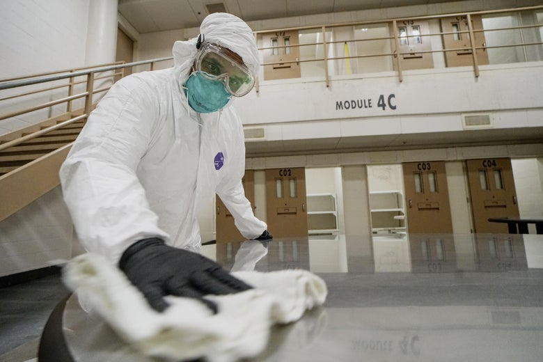 A man in a protective suit, goggles and mask scrubs the floor of a jail.