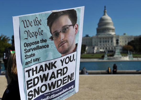 Demonstrators hold placards supporting former US intelligence analyst Edward Snowden during a protest against government surveillance on October 26, 2013 in Washington, DC.