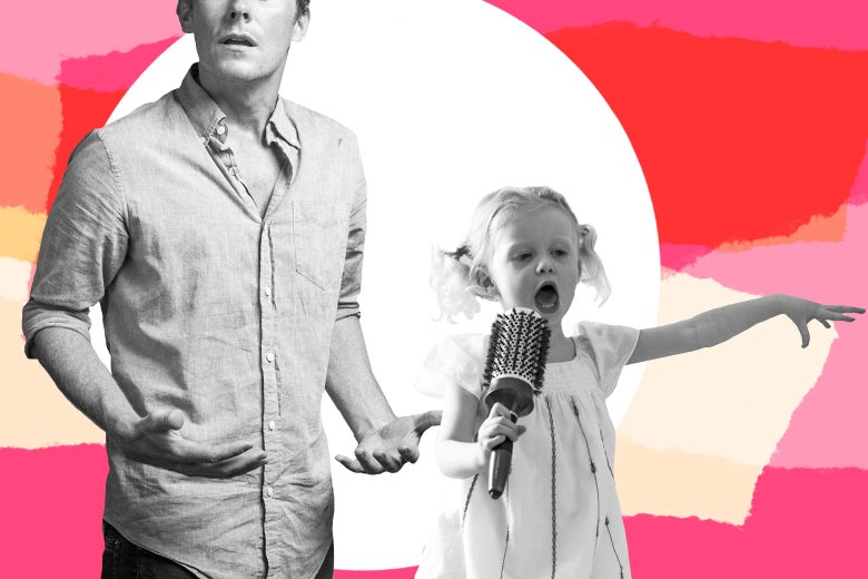 A dad looks annoyed while his young daughter in pigtails boisterously sings into a hairbrush.