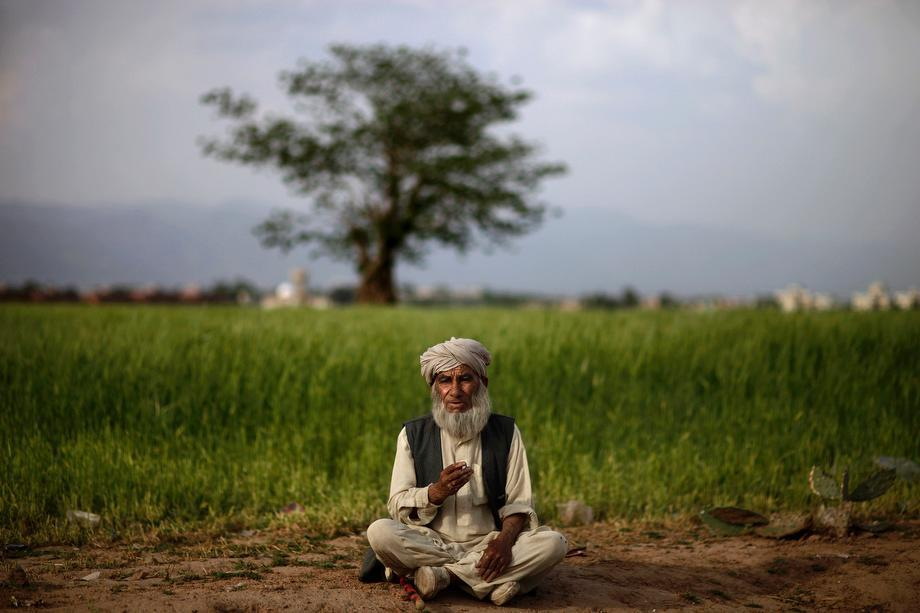 Afghan refugee Abdulkareem Khan, 80, smokes a cigarette while watching his sheep, not pictured, feeding in a field on the on the outskirts of Islamabad, Pakistan on April 3, 2013.