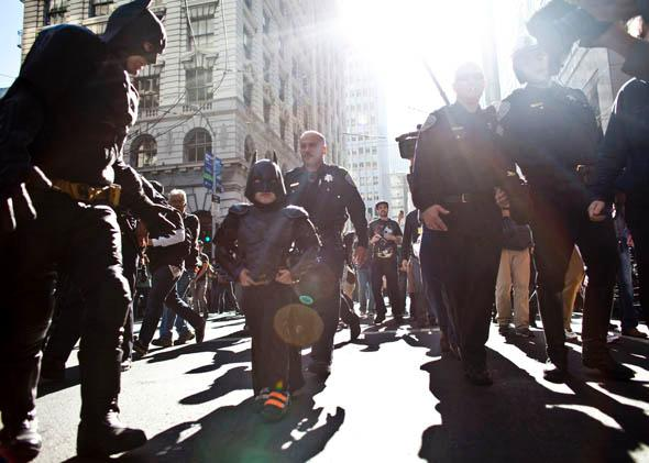 Police escorts 5-year-old leukemia survivor Miles, also known as BatKid and Batman after they arrest the Riddler November 15, 2013 in San Francisco.