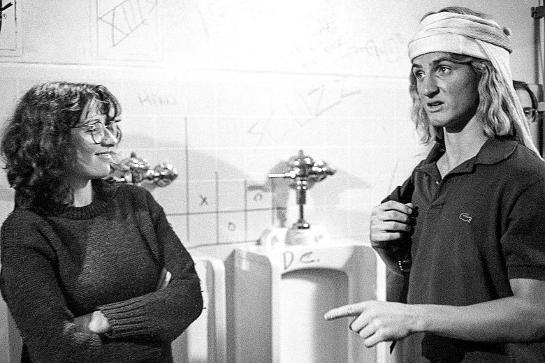 Black and white photo of Heckerling smiling with arms crossed at Penn as Spicoli wearing a polo and backpack in a boys bathroom with a row of urinals behind them