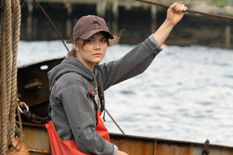 A young woman sits on a fishing boat in orange coveralls and a baseball cap.