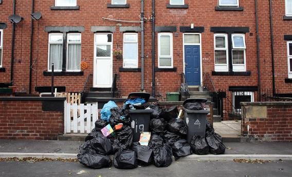 Overflowing refuse bins litter the streets.