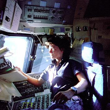 American astronaut Sally K. Ride, mission specialist on STS-7, monitors control panels from the pilot's chair on the Flight Deck, June 25, 1983.