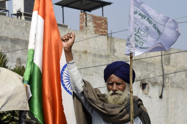 A Sikh man raises his fist and carries a flag next to an Indian flag.
