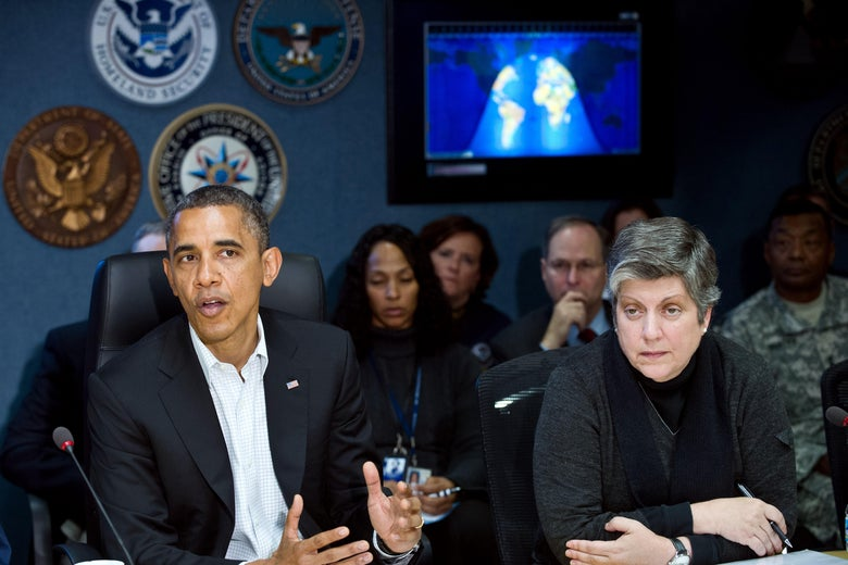 Obama speaks as Napolitano sits next to him at a conference table. A map is projected behind them.