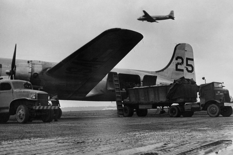 Trucks load planes on a tarmac as another plane flies by.