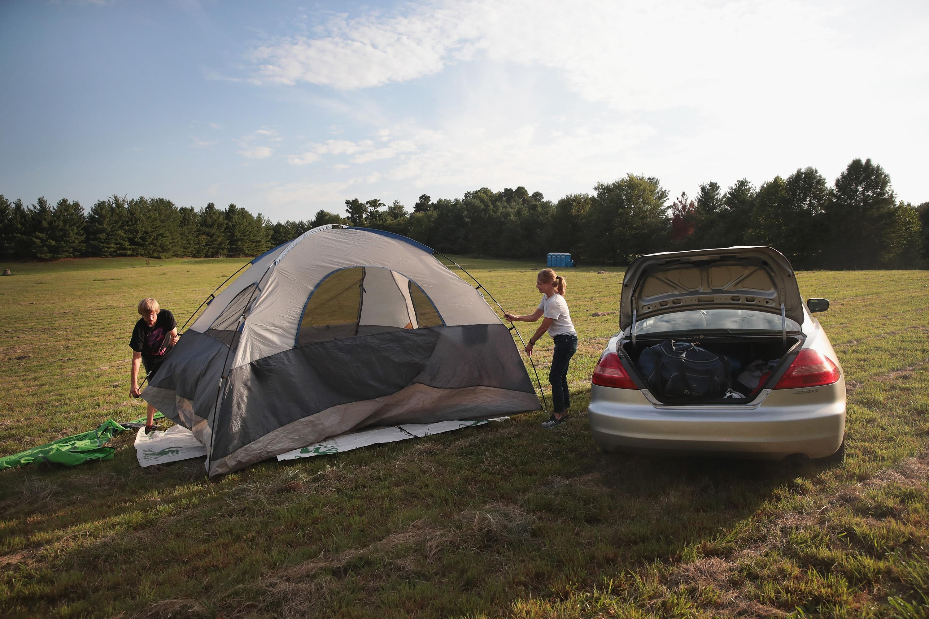 Karen Just and her son Mathew pitch a tent in a hay field which had been converted into a campground to host visitors for Monday's solar elclipse on August 18, 2017 near Carbondale, Illinois.