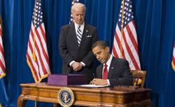 US Vice President Joe Biden stands behind US President Barack Obama as he signs the American Recovery and Reinvestment Act. Click image to exand.