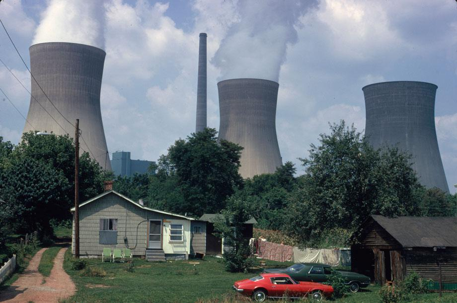 "Water cooling towers of the John Amos Power Plant loom over Poca, WV, home that is on the other side of the Kanawha River. Two of the towers emit great clouds of steam."" Harry Schaefer, Poca, West Virginia, August 1973"