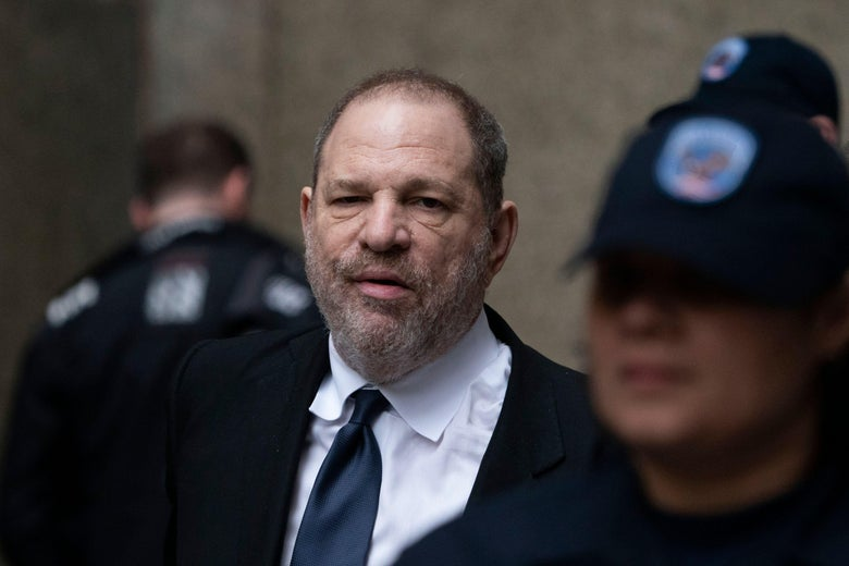 Harvey Weinstein, dressed for court, can be seen standing around police officers.