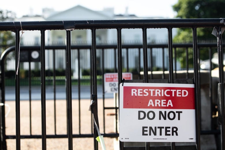 """The White House is seen through a closed black gate on which a sign says """"restricted area, do not enter."""""""