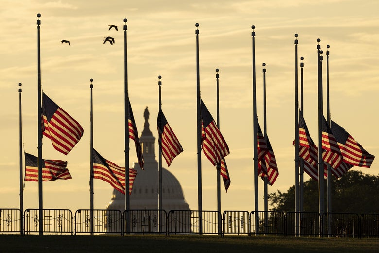 American flags are flown at half-staff with the capitol dome in the background.