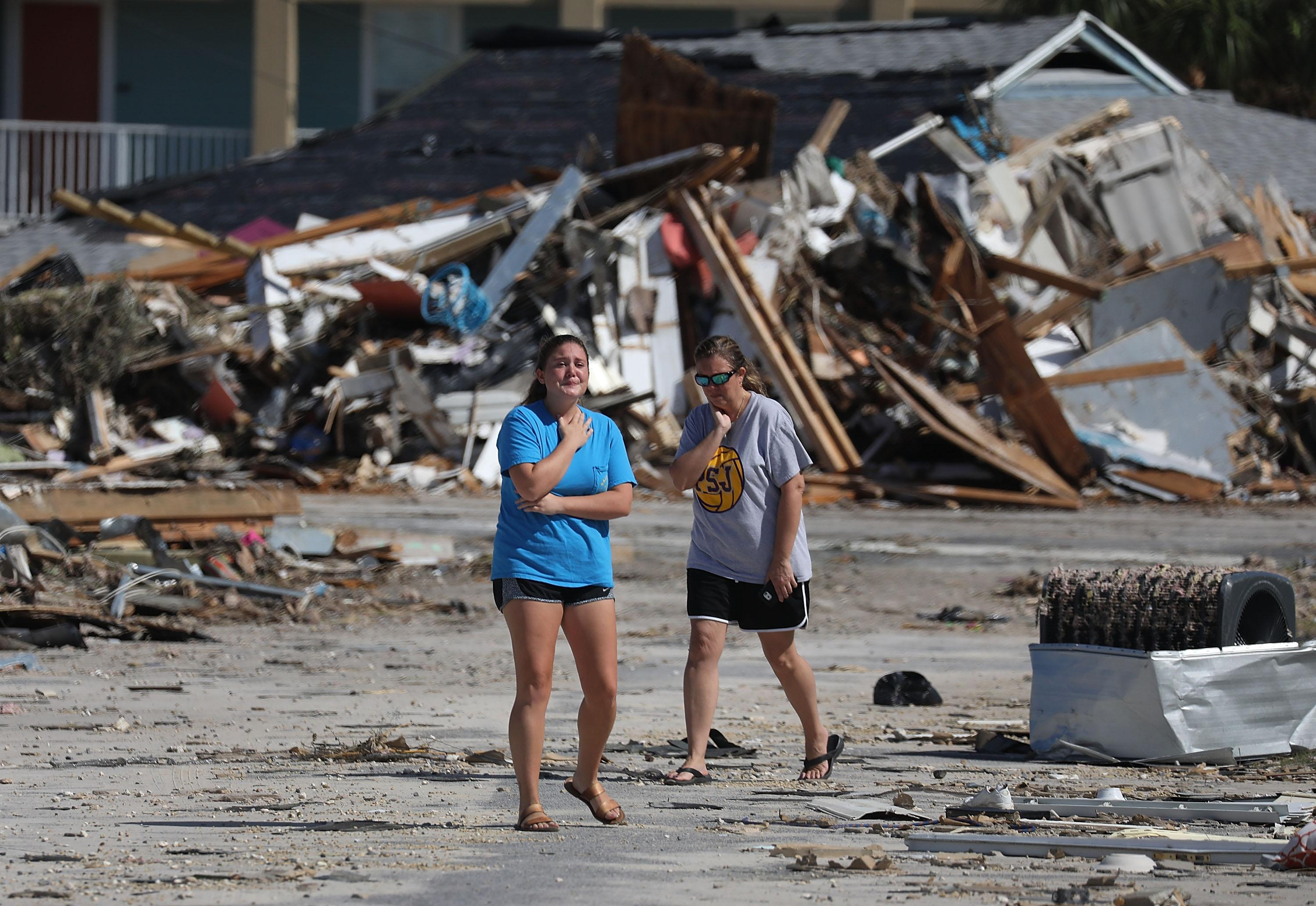 Two women in T-shirts and flip-flops appear upset as they stand before the wreckage of a house.