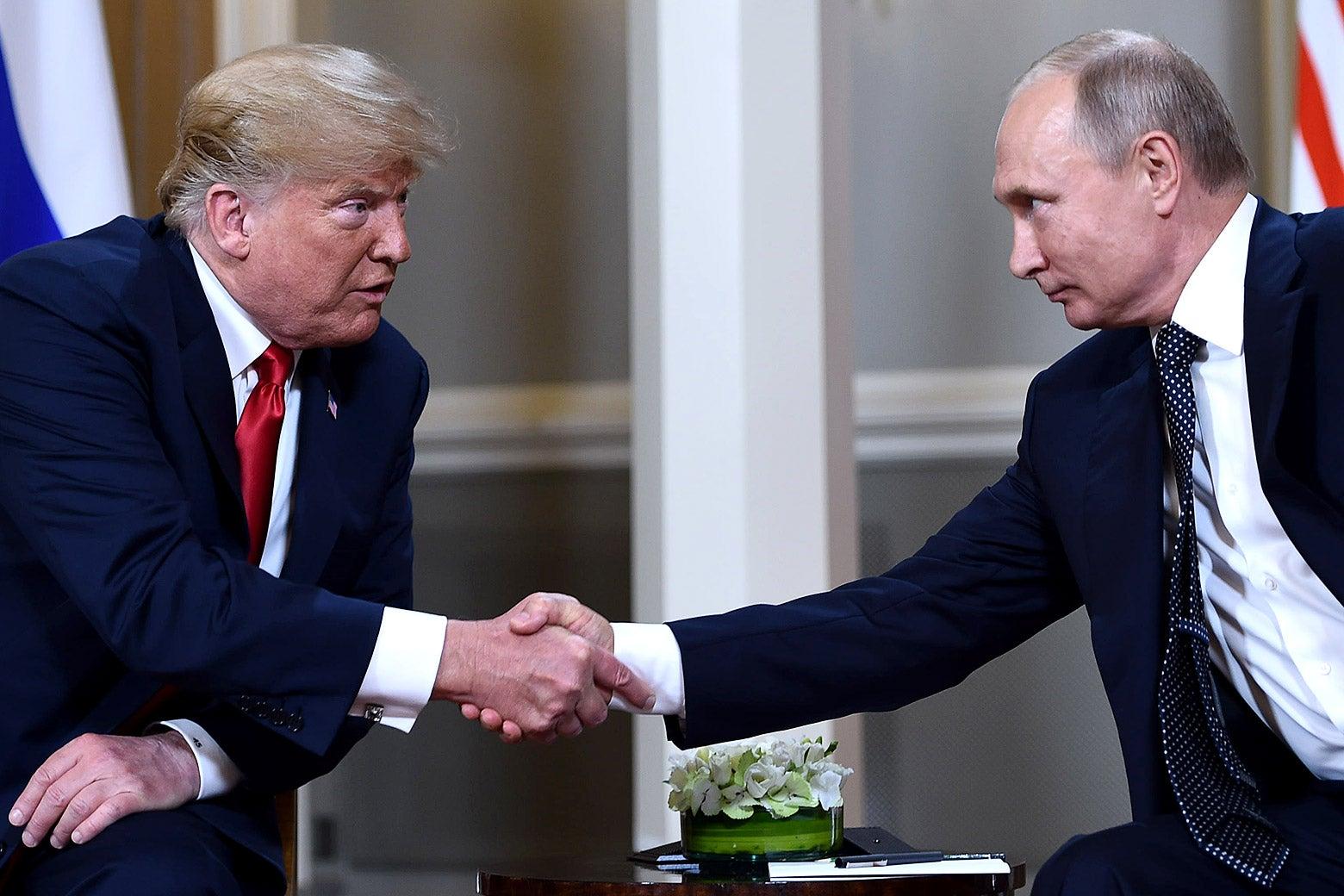 Donald Trump and Vladimir Putin, seated, shake hands.