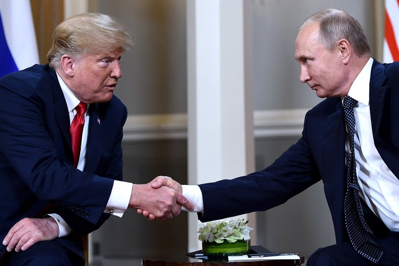 Donald Trump and Vladimir Putin, seated, shake hands.