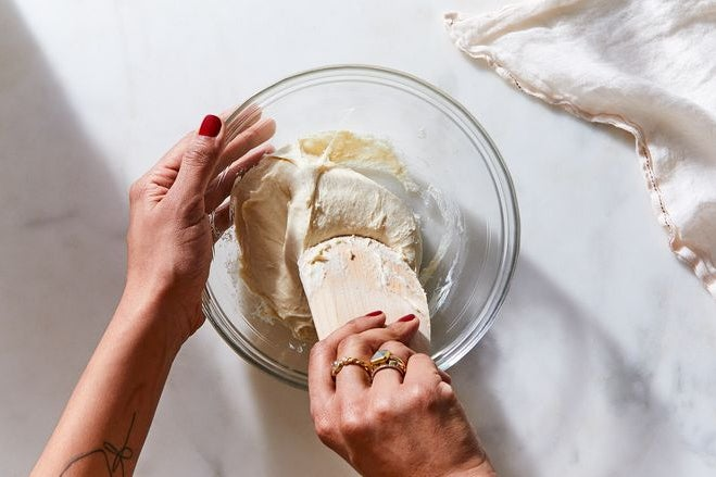 Hands use a wooden spatula to knead dough in a glass bowl.