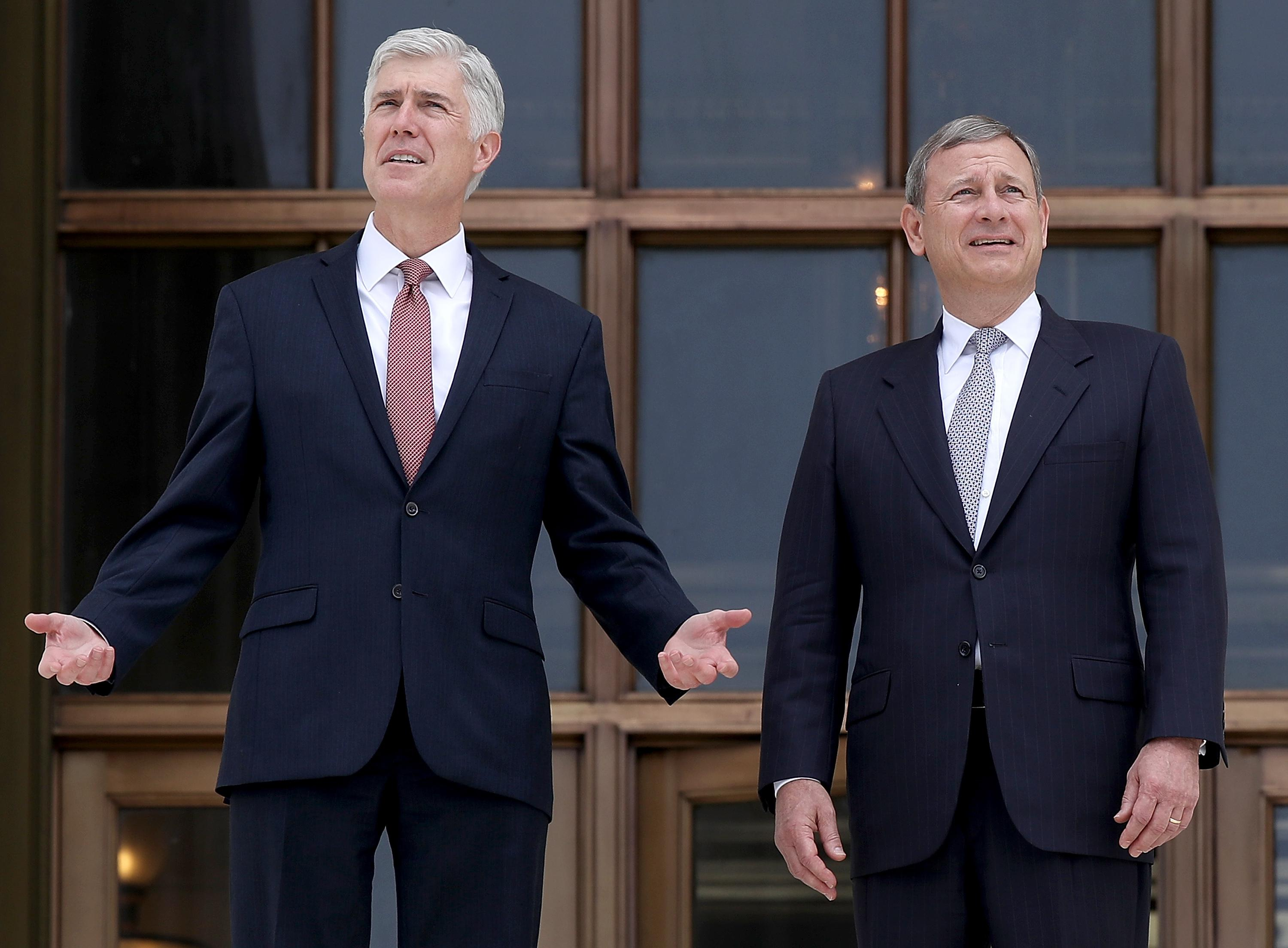 Neil Gorsuch and John Roberts talking to each other in front of the Supreme Court.