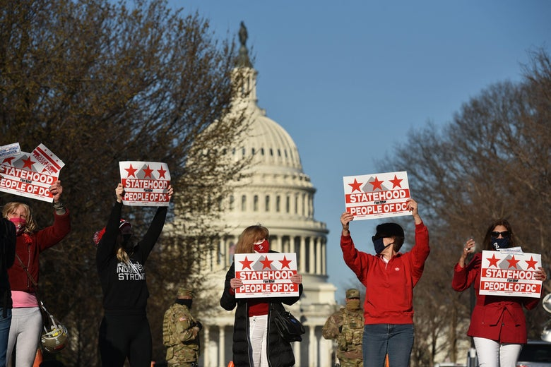 """Demonstrators hold signs that say """"Statehood for the People of D.C."""" The Capitol dome can be seen behind them."""