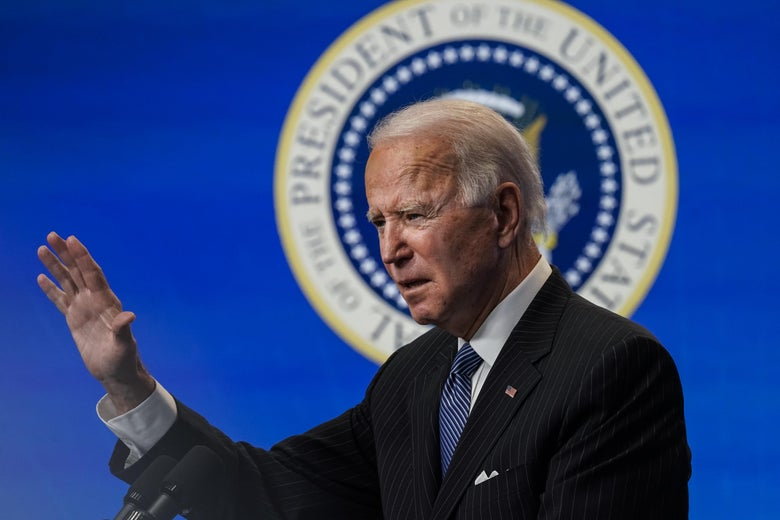 Joe Biden raises a hand while speaking at a podium with the presidential seal behind his head.